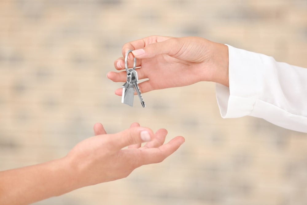 Ejendomsmægler der overrækker nøgler